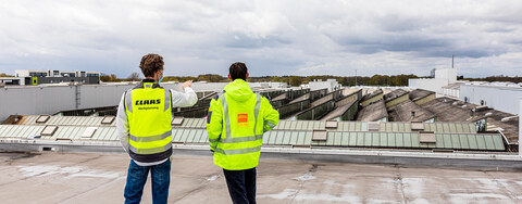 Björn Evers, Leitung Werkplanung bei Claas, und Stefan Bastian, Projektleiter bei Köster am Standort Bielefeld, (v.l.n.r.) besprechen die Baumaßnahme auf dem Dach einer Produktionshalle am Claas-Standort in Harsewinkel.